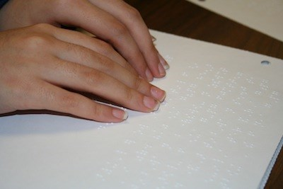 Image shows a pair of hands reading hard copy braille