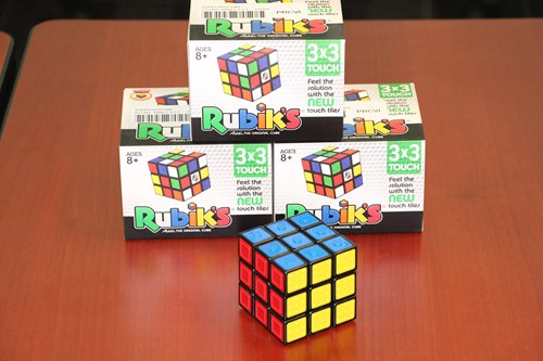 Image shows one Rubik's touch cube in the foreground with three product boxes stacked in the background.