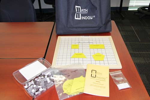 Images shows the contents of the Math Window kit. Shapes tiles are placed on the board in the foreground.