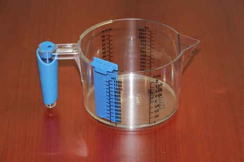 Image of tactile measuring cup with non-slip and accessible level gauge on the side of the cup.