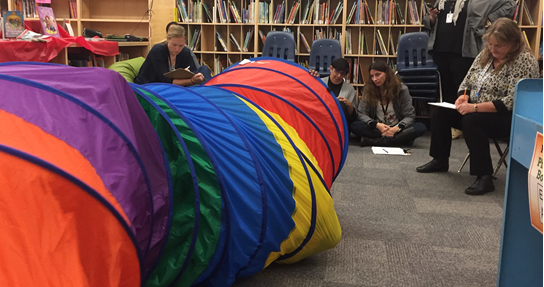 Image shows the TPBVDA team observing a student playing in a multi-coloured play tunnel.