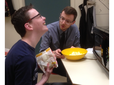 Images shows a student laughing while pouring a bowl of popped popcorn