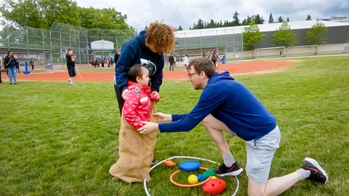 Image shows a student in a burlap sack participating in a sack race with support from adults