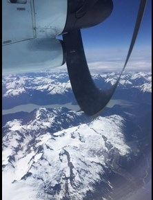 Photo shows an airplane propeller in the foreground an an airborne view of snowy mountaintops in the background.