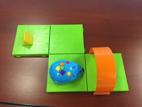 Photo shows a programmable robot mouse on a track made of interlocking plastic squares. A target plastic piece of cheese sits nearby.