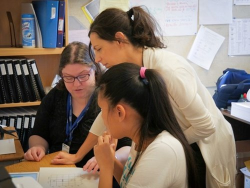 Two teachers of students with visual impairments and one student examine the accessible coding materials
