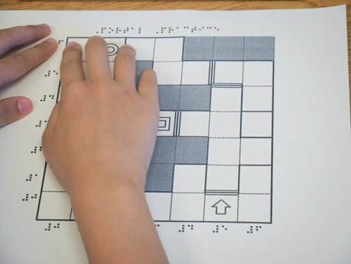 Photo shows a student's hands exploring the tactile diagram of the Swift Playground grid.