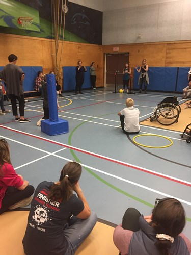 Photo shows teachers demonstrating an adaptive sport in a gymnasium
