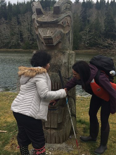 Photo shows a student and a teacher exploring a totem pole.