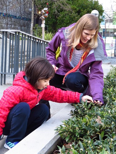 Photo shows a student and teacher exploring a shrubbery together.