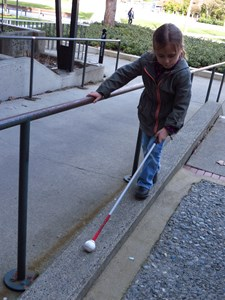 Photos shows a student using a mobility cane to navigate a narrow walkway.