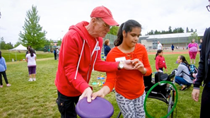 Image shows a TSVI showing a student how to throw a frisbee.
