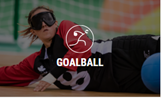 Photo shows a goalball player diving to stop the ball.