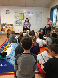 A teacher reads a story to an elementary class with students seated on a carpet.